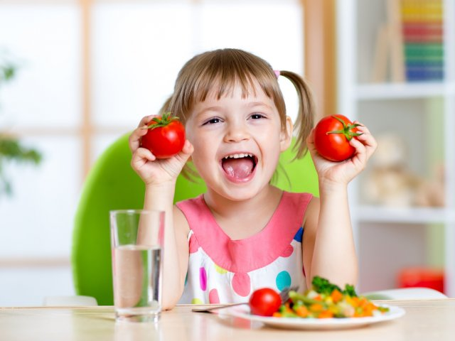 Portrait of happy child with vegetables